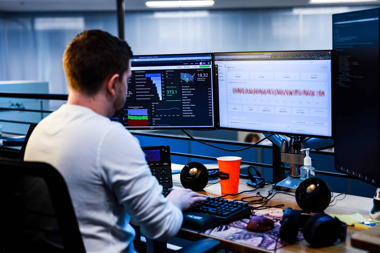 Man looking at data on three computer screens