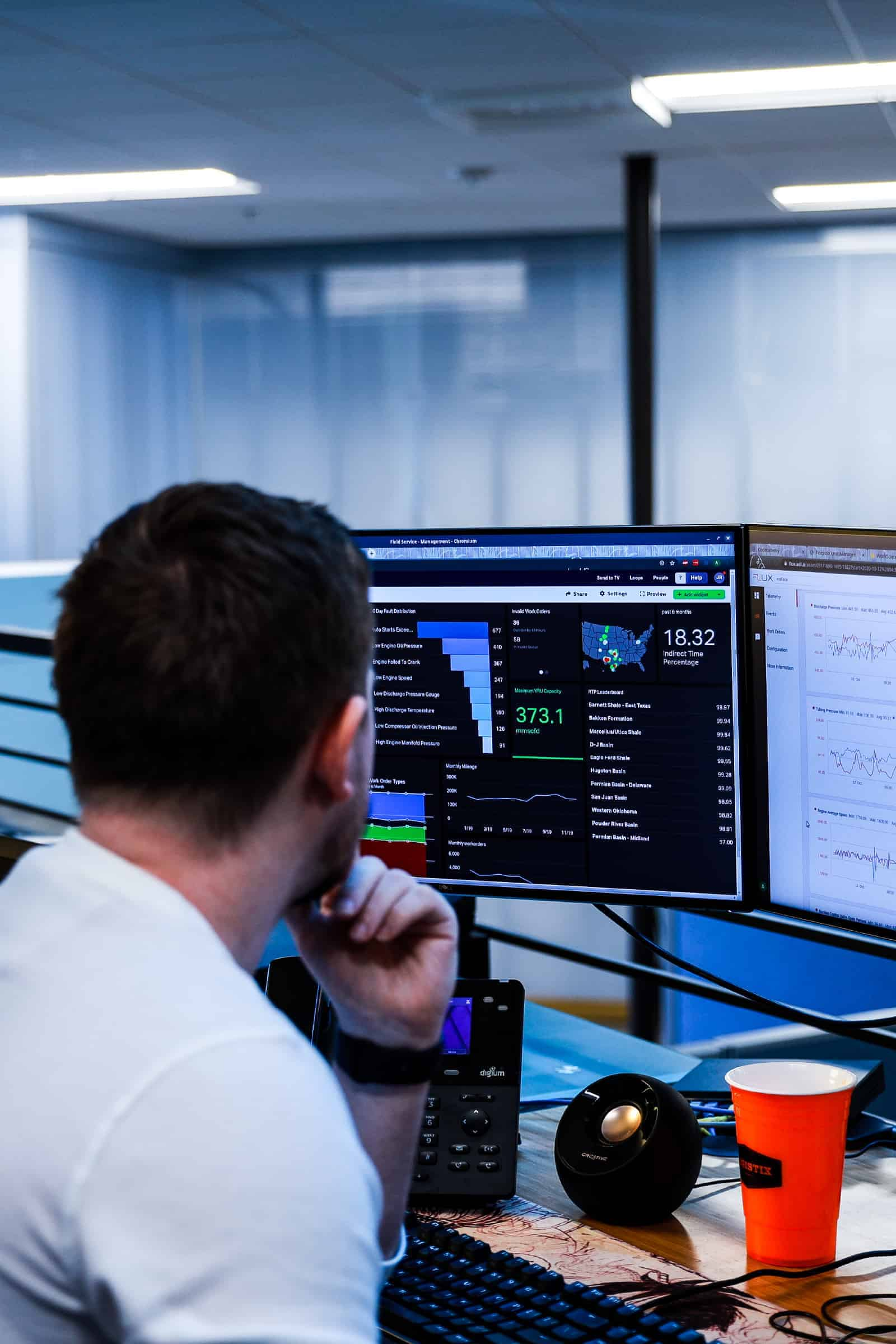 Man looking at computer screens with data