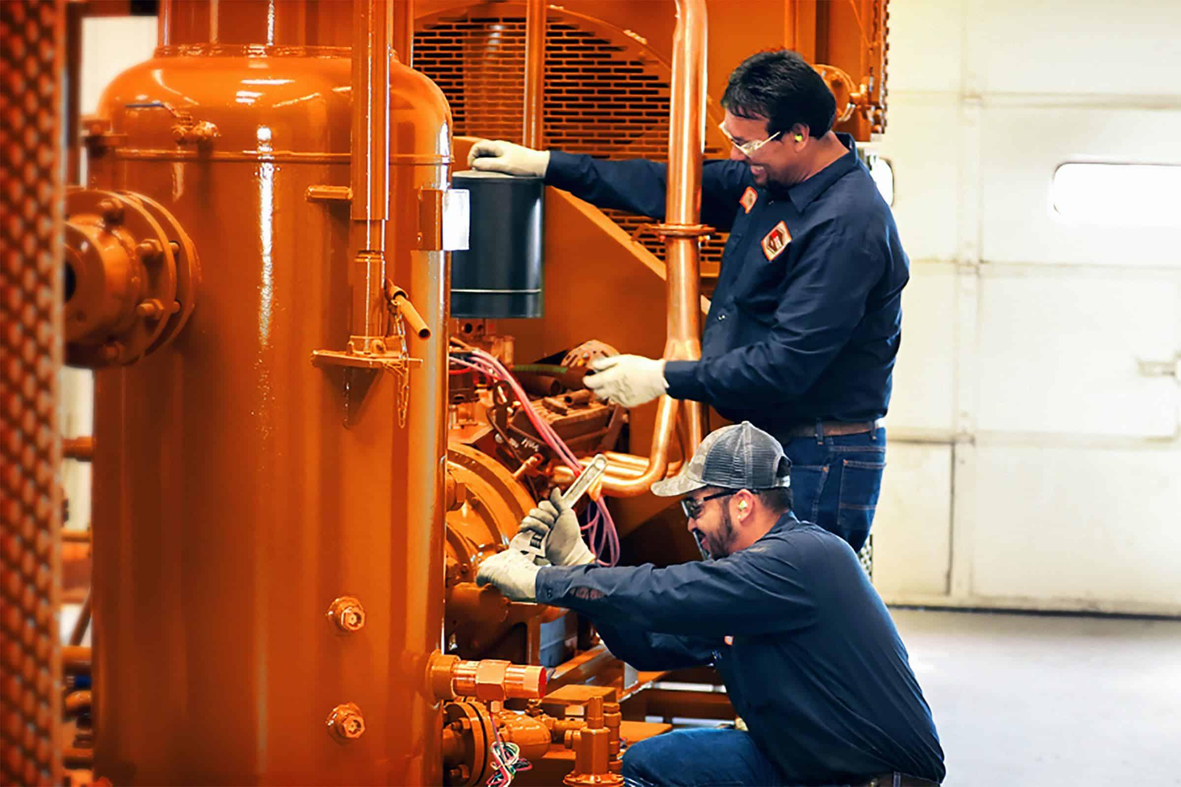 2 men in PPE working on equipment